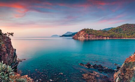 Few minutes before sunrise on Mediterranean sea in April. Colorful morning scene of small bay near Tekirova village, District of Kemer, Antalya Province. Beauty of nature concept background.