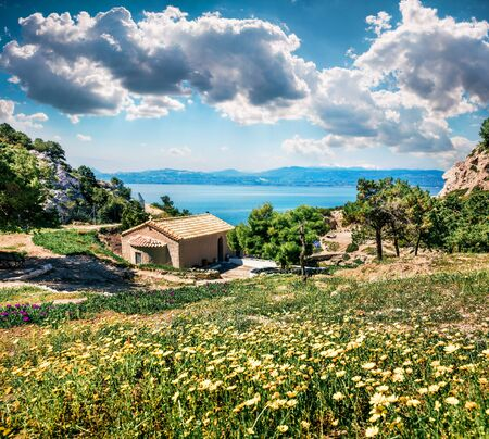 Sunny spring scene of Agios Ioannis Church. Splendid morning view of West Court of Heraion of Perachora, Limni Vouliagmenis location, Greece, Europe. Traveling concept background.