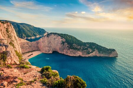 Colorful spring view of Navagio beach with shipwreck. Sunny evening seascape of Ionian Sea, Zakynthos (Zante) island, Greece, Europe. Beauty of nature concept background.