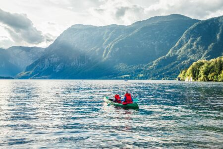 Couple paddling a kayak. Wonderful summer scene of Bohinj lake, Triglav National park. Sunny morning view of Julian Alps, Slovenia. Concept for adventure, travel, action, lifestyle. Stock fotó
