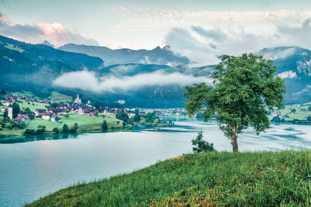 Foggy summer scene of Lungerersee lake. Bright morning view of Swiss Alps, Lungern village location, Switzerland, Europe. Traveling concept background.