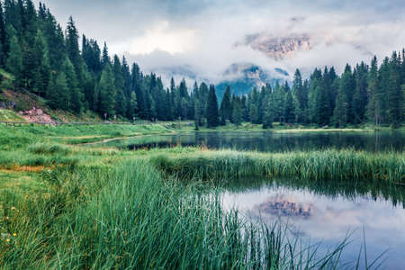 Majestic summer scene of Antorno lake with Tre Cime di Lavaredo (Drei Zinnen) mount in the morning mist. Incredible morning view of Dolomite Alps, Italy, Europe. Beauty of nature concept background.