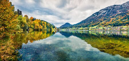 Panoramic autumn view on Grundlsee lake. Gloomy morning scene of Brauhof village, Styria stare of Austria, Europe. Colorful view of Alps. Traveling concept background.