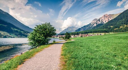 Colorful summer view of San Valentino village from Muta lake (Haidersee). Great morning scene of Italian Alps, Italy, Europe. Traveling concept background.