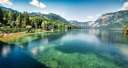 First sunlight glowing surface of Bohinj lake. Spectacular summer panorama of Triglav national park. Great morning view of Julian Alps, Slovenia, Europe. Traveling concept background. Stock fotó