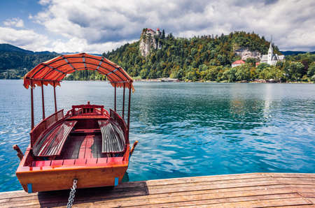 Attractive summer view of Lake Bled (Blejsko jezero) is a glacial lake in the Julian Alps in northwestern Slovenia. Sunny morning scene of Bled town and is overlooked by Bled Castle. Zdjęcie Seryjne