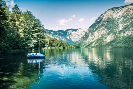 First sunlight glowing surface of Bohinj lake. Beautiful summer scene of Triglav national park. Great morning view of Julian Alps, Slovenia, Europe. Traveling concept background.