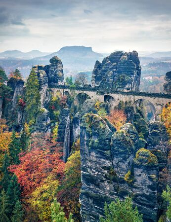 Rainy autumn view of Bastei bridge. Picturesque morning scene of Saxon Switzerland National Park, Germany, Europe. Beauty of nature concept background.
