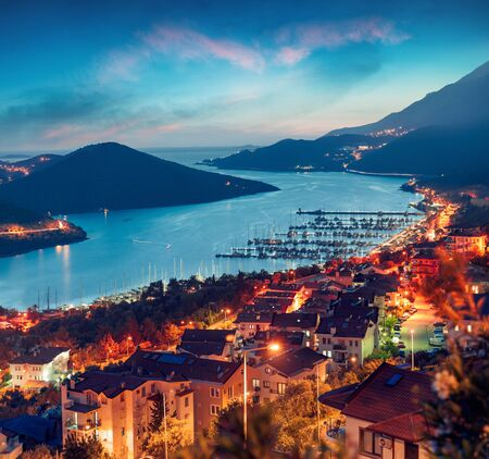 View from the birds eye of the Kas city, district of Antalya Province of Turkey, Asia. Colorful spring sunset in small Mediterranean yachting and tourist town. Traveling concept background.