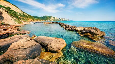 Sunny spring view of small port in Gardenos village. Stunning morning seascape of Ionian Sea. Wonderful landscape of Corfu island, Greece, Europe. Traveling concept background.