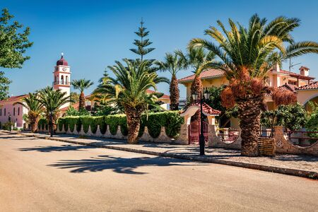 Amazing spring view of the street of Karavomylos village with St. John church on background. Sunny morning scene of Kefalonia island, Greece, Europe. Traveling concept background.