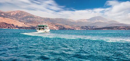Panoramic view of Ionian island - Cephalonia. Ferry ship from Lixouri to capital of island - Argostolion. Beautiful spring seascape of Mediterranean sea. Traveling concept background. Stock Photo