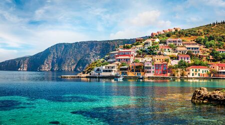 Sunny morning cityscape of Asos village on the west coast of the island of Cephalonia, Greece, Europe. Colorful spring sescape of Ionian Sea. Traveling concept background.