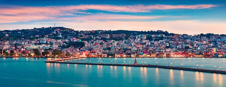 Panoramic evening cityscape of Argostolion town, former municipality on the island of Kefalonia, Ionian Islands, Greece. Impressive spring seascape of Ionian Sea. Traveling concept background.