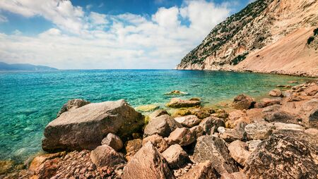 Sunny view of Myrtos Beach. Colorful morning scene of Cephalonia island, Divarata village location, Greece, Europe. Bright spring seascape of Ionian Sea. Beauty of nature concept background. Stock Photo
