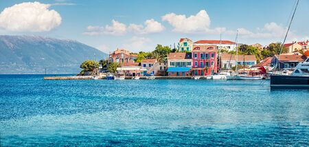 Panoramic spring view of Fiskardo port. Colorful morning seascape of Ionian Sea. Bright outdoor scene of Kefalonia island, Greece, Europe. Traveling concept background. Stock Photo