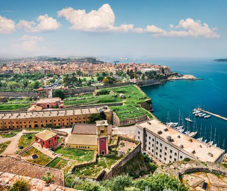 Aerial view of the capital of Corfu island. Colorful spring cityscape of Kerkira town. Sunny morning seascape of Ionian Sea, Greece, Europe. Traveling concept background.