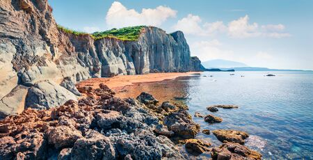 Splendid spring landscape of famous Xi Beach. Sunny morning scene of Cephalonia island, Greece, Europe. Attractive seascape of Ionian Sea. Traveling concept background.