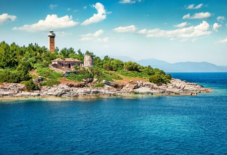 Colorful panoramic view of old Venetian lighthouse. Slpendid morning seascape of Ionian Sea. Wonderful outdoor scene of Kefalonia island, Fiskardo village, Greece, Europe. Traveling concept background. Stock Photo