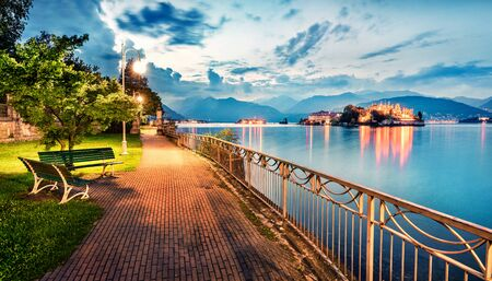 Splendid evening cityscape of Stresa town. Wonderful summer susnset on Maggiore lake with Bella island on background, Province of Verbano-Cusio-Ossola, Italy, Europe. Traveling concept background. Stockfoto