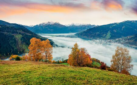 Fantastic view of Zell lake. Impressive autumn sunrise of Austrian town - Zell am See, south of the city of Salzburg. Beauty of nature concept background.