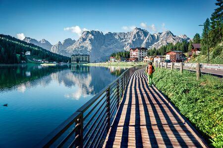 Tourist walking on the pier on Misurina lake. Sunny morning scene of Misurina resort, National Park Tre Cime di Lavaredo, Location Auronzo, Dolomiti Alps, South Tyrol, Province of Belluno, Italy, Europe.