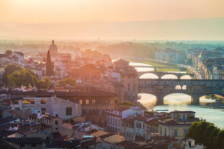 Colorful evening cityscape of Florence, Italy, Europe.  Beautiful medieval arched river bridge with Roman origins - Ponte Vecchio over Arno river.Traveling concept background. Stock Photo