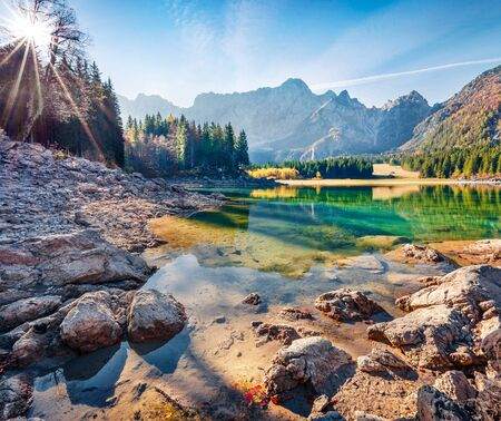 Splendid autumn view of Fusine lake. Bright morning scene of Julian Alps with Mangart peak on background, Province of Udine, Italy, Europe. Traveling concept background.