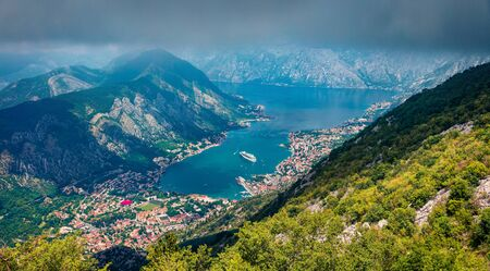 Dramatic summer cityscape of Kotor port. Aerial morning view of Kotor bay and  limestone cliffs of Mt. Lovcen. Sunny Adriatic seascape. Beautiful world of Mediterranean countries. Traveling concept background.