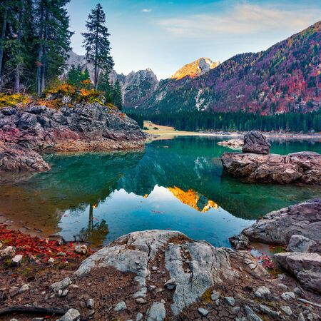 Great autumn view of Fusine lake. Colorful morning scene of Julian Alps with Mangart peak on background, Province of Udine, Italy, Europe. Traveling concept background.