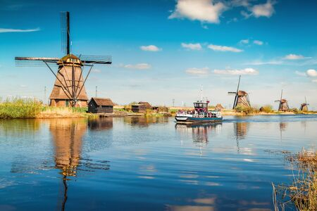 Walking boat on the famoust Kinderdijk canal with windmills. Old Dutch village Kinderdijk. Netherlands, Europe. Stock Photo
