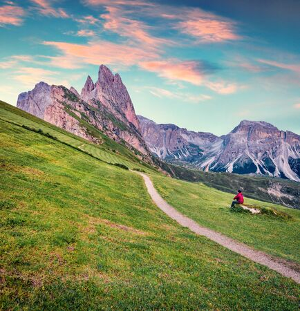 Hiker admires the fantastic sunrise with Furchetta peak on background. Attractive summer scene of Funes Valley. Stunning evening in Puez Odle National Park, Dolomiti Alps, South Tyrol, Italy, Europe.