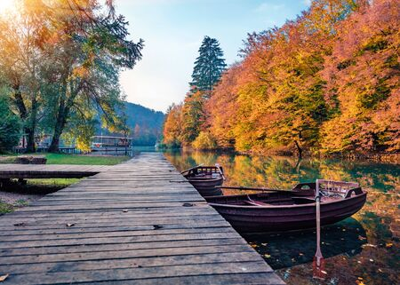 Wonderful evening view of pure water lake with boats in Plitvice National Park. Amazing autumn sunset in Croatia, Europe. Beauty of nature concept background. Stock Photo