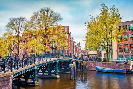 Captivating autumn scene of Amsterdam city. Famous Dutch channels and great cityscape. Gloomy morning landscape in Netherlands, Europe. Traveling concept background. Stock fotó