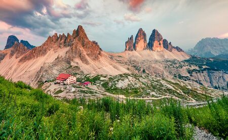 Colorful evening scene of Tre Cime Di Lavaredo mountain peaks. Incredible summer sunset in Dolomiti Alps, South Tyrol, Italy, Europe. Beauty of nature concept background.