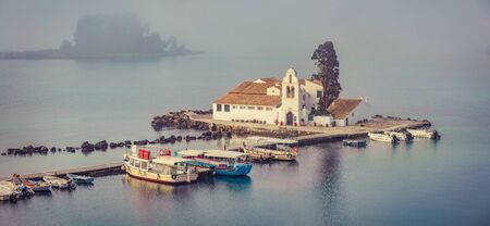 Misty sunrise view of Vlacherna Monastery. Picturesque morning cityscape of Kerkira town, capital of Corfu island, Greece, Europe. Panoramic summer seascape of Ionian Sea. Retro style filtered. Stock Photo
