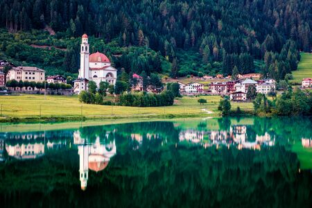 Picturesque evening view of Parrocchia di San Lucano Vescovo Catholic Church. Nice summer scene of Santa Caterina lake and Auronzo di Cadore resort, Italy, Europe. Traveling concept background.