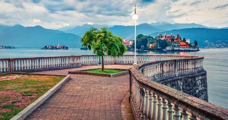 Empty city park in Stresa town. Wonderful summer susnset on Maggiore lake with Bella island on background, Province of Verbano-Cusio-Ossola, Italy, Europe. Traveling concept background.