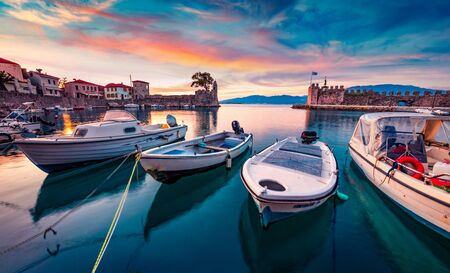 Sunrise in popular touristic destination - Nafpaktos port. Fantastic morning view of Gulf of Corinth, Greece, Europe. Fantastic seascape of Ionian sea. Traveling concept background.