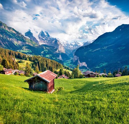 Old chalet on the lawn in Wengen village. Green morning scene of countryside in Swiss Alps, Bernese Oberland in the canton of Bern, Switzerland, Europe. Beauty of nature concept background.