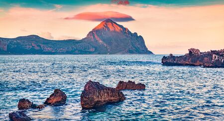 Colorful summer sunrise in Monte Cofano natural park. Incredible morning view of Sicily, Macari village location, San Vito cape, Province of Trapani, Italy, Europe. Seascape of Mediterranean sea.