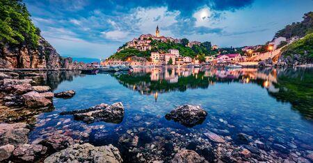 After a hot day, a small resort town Vrbnik is relaxing. Splendid summer seascape of Adriatic sea, Krk island, Kvarner bay archipelago, Croatia, Europe. Beautiful world of Mediterranean countries. Imagens