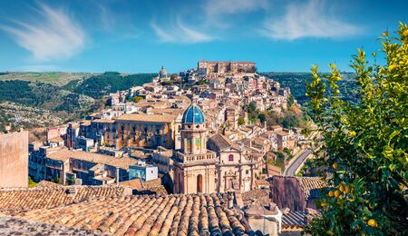 Sunny spring cityscape of Ragusa town with Palazzo Cosentini and Duomo di San Giorgio church on background. Nice afternoon scene of Sicily, Italy, Europe. Traveling concept background.