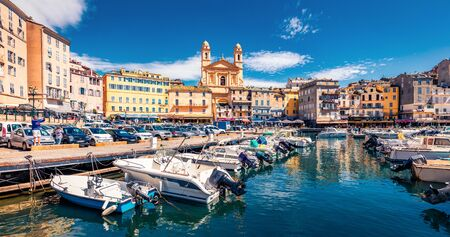 Panoramic summer cityscape of Bastia port with twin-towered Church of St. Jean-Baptiste rising behind it. Stunning afternoon view of Corsica island, France, Europe. Bright Mediterranean seascape.