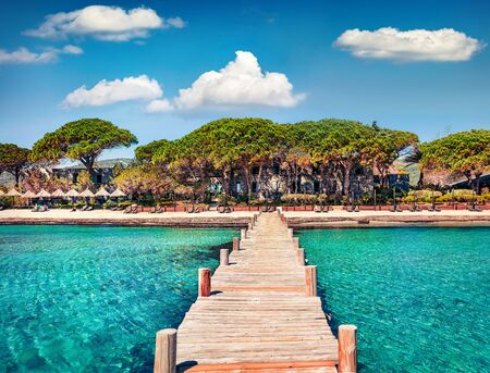 Magnificent summer view of wooden pier on Santa Giulia beach. Romantic morning scene of Corsica island, France, Europe. Splendit Mediterranean seascape. Beauty of nature concept background.