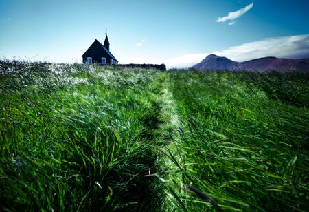 Black wooden Budakirkja church at Saefellsnes. Gorgeous summer morning with field of fresh green grass on Snafellsnes peninsula, western Iceland, Europe. Traveling concept background.