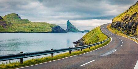 Gloomy summer scene of Faroe Islands and Tindholmur cliffs on background. Panoramic morning view of Vagar island, Kingdom of Denmark, Europe. Traveling concept background.
