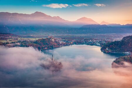 Fantastic sunrise on Bled lake. Misty morning view of church of Assumption of Maria on Bled lake. Foggy autumn landscape in Julian Alps, Slovenia, Europe. Traveling concept background. Foto de archivo