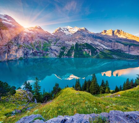 First sunlight gloving mountain hills and meadows. Picturesque summer view of unique Oeschinensee Lake. Sunrise in Swiss Alps with Bluemlisalp mountain on background, Switzerland, Europe.