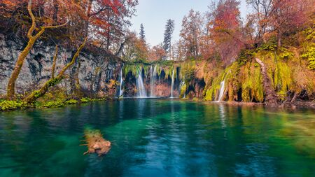 Last warm autumn days in Plitvice National Park. Picturesque autumn scene of pure water lake and waterfalls in Croatia, Europe. Beauty of nature concept background.